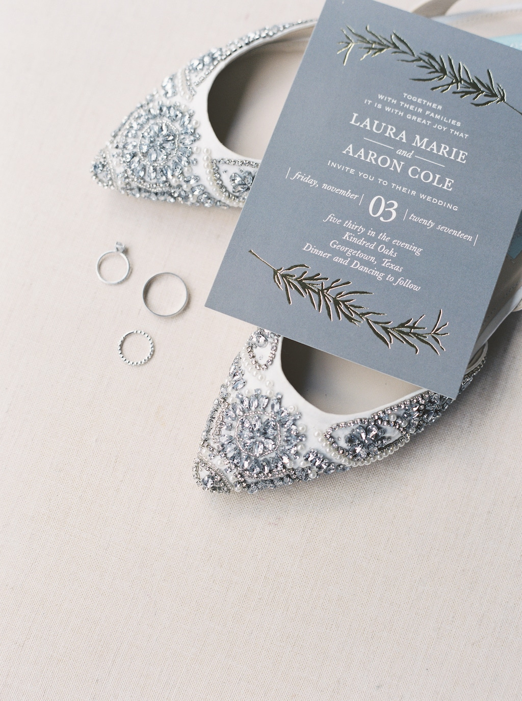 An invitation to a wedding at Kindred Oaks in Georgetown, Texas, rests on top of a pair of glamorous bridal shoes, next to the bride and groom's wedding rings.