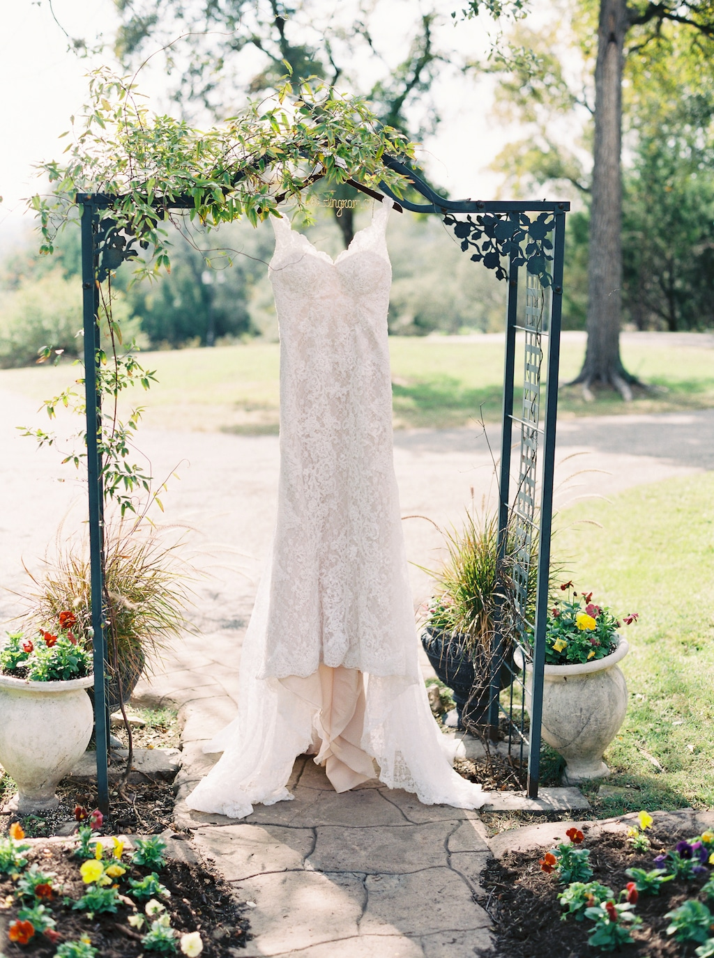 A lacy wedding dress hangs from a small green arbor on the grounds of a wedding venue in Georgetown, Texas.