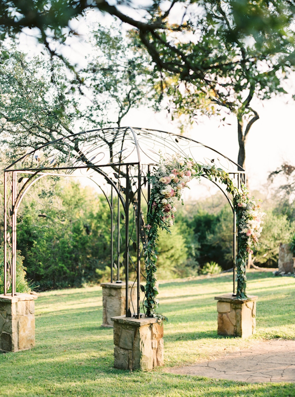Sun shines on a ceremony arbor at Kindred Oaks, a wedding venue in Georgetown, Texas.