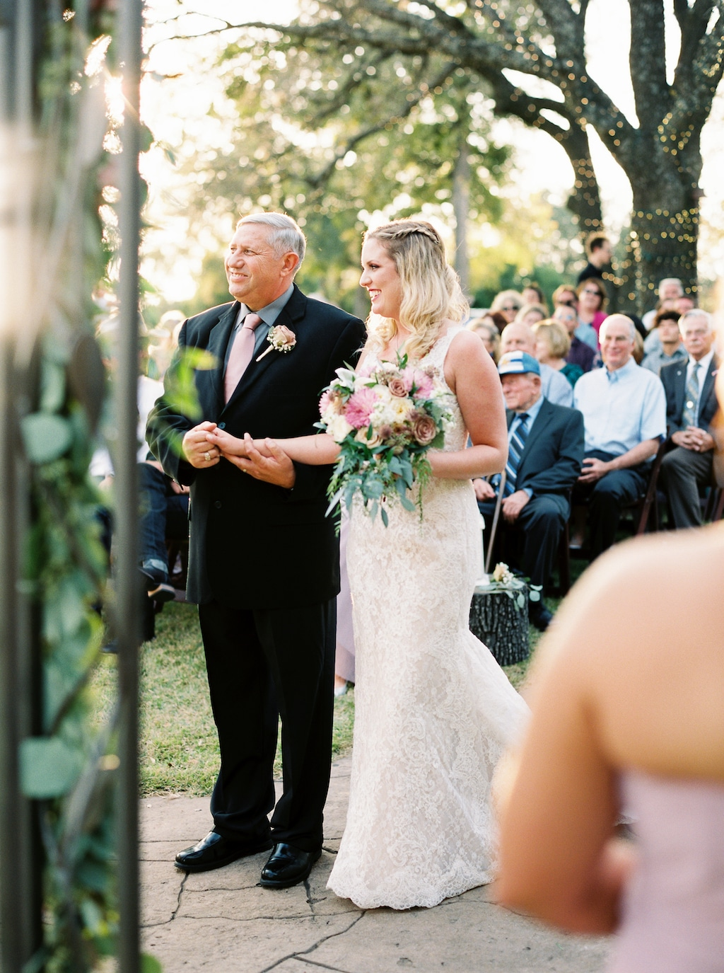 A smiling bride and her father stand at a Georgetown, Texas wedding ceremony while guests look on from behind.