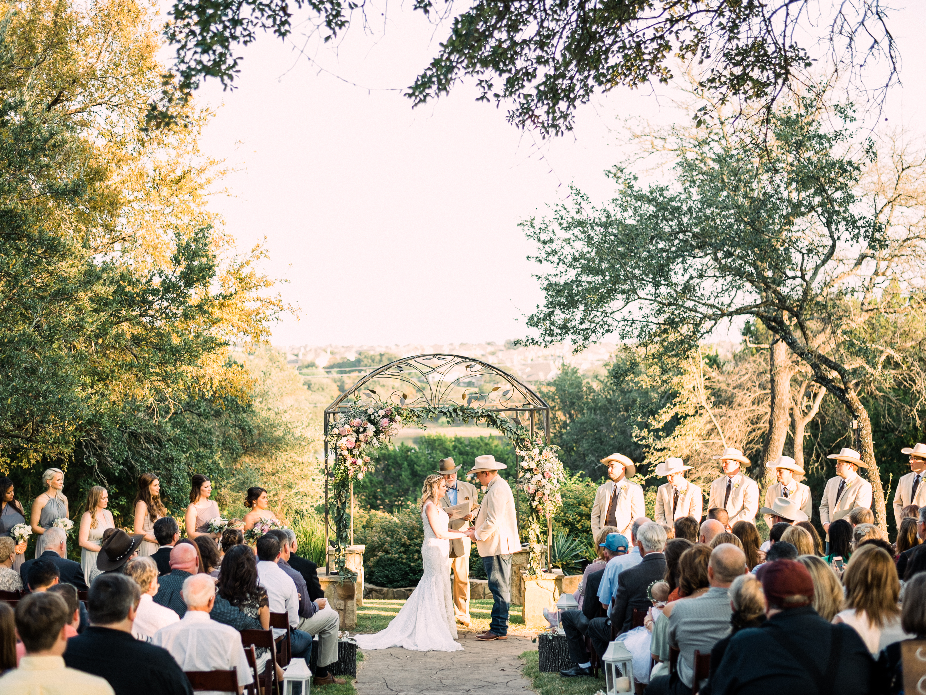 A bride and groom face each other while they say their vows during their sunny, outdoor wedding ceremony in Georgetown, Texas.