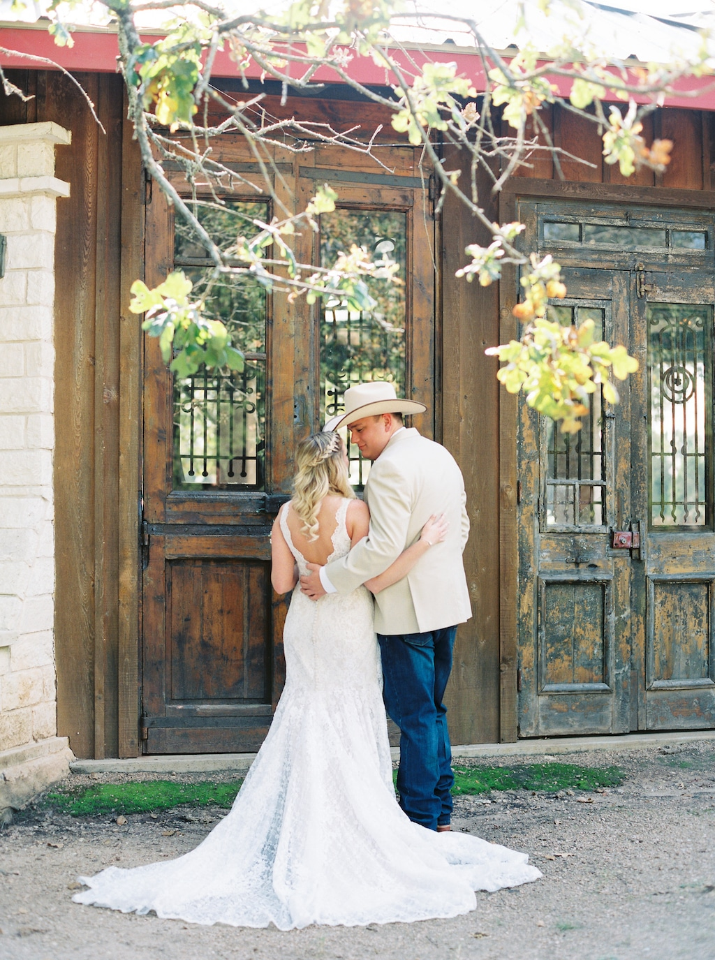 A bride and groom, with their backs to the camera, hug each other next to pairs of weathered doors outside at a Georgetown, Texas wedding venue.