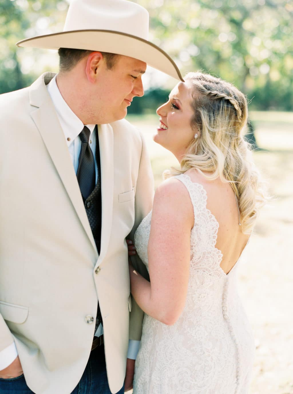 A bride and groom smile at each other as they take wedding portraits at a Georgetown, Texas wedding venue.