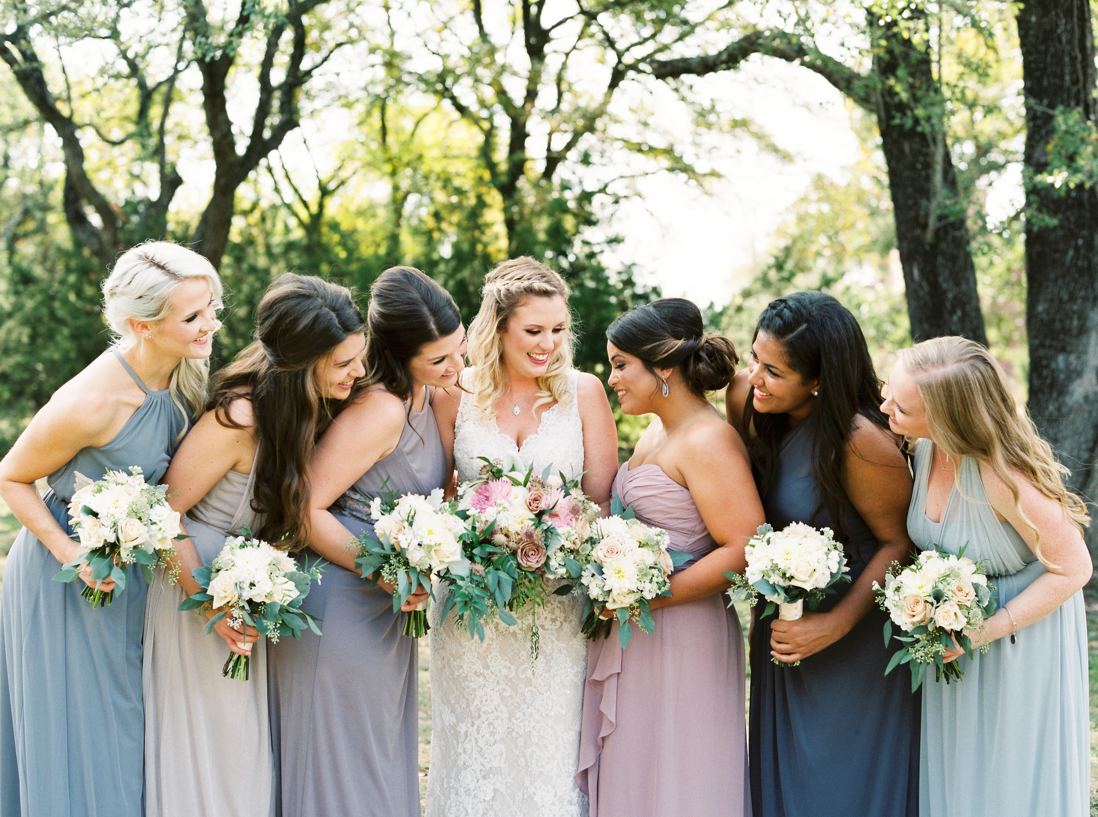 A bride and her six bridesmaids, wearing different shades of blue, stand smiling together on the grounds of Georgetown, Texas wedding venue, Kindred Oaks.