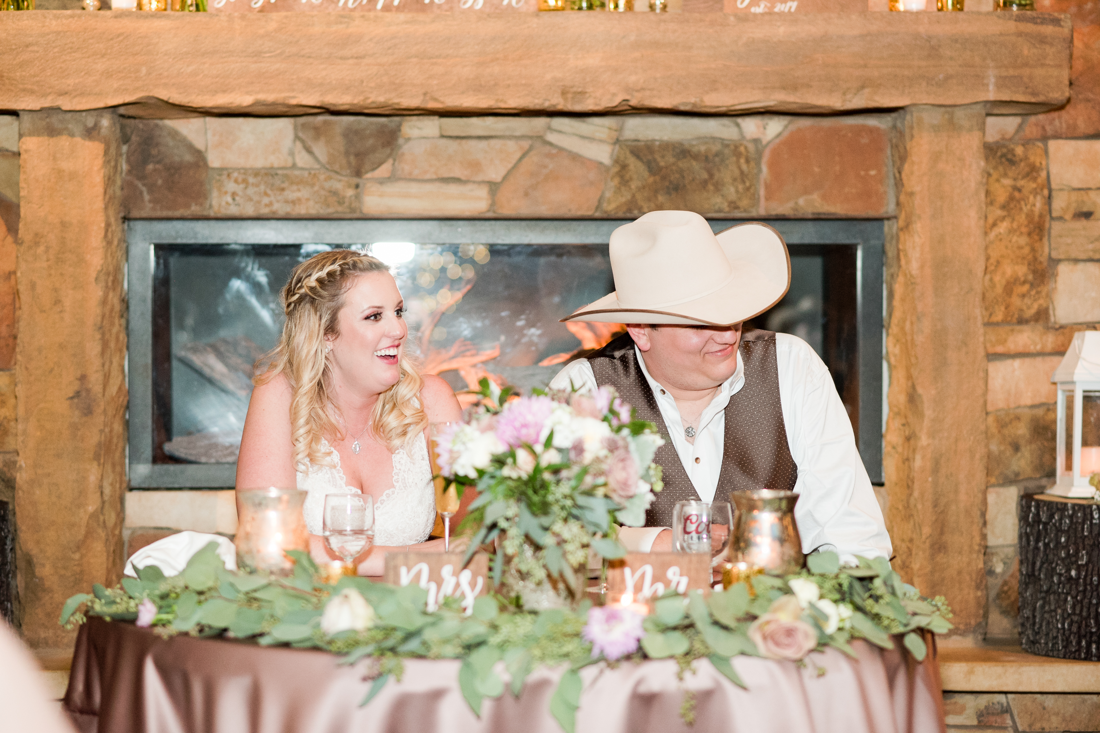 A bride and groom sit at their sweetheart table during their wedding reception at Kindred Oaks in Georgetown, Texas.