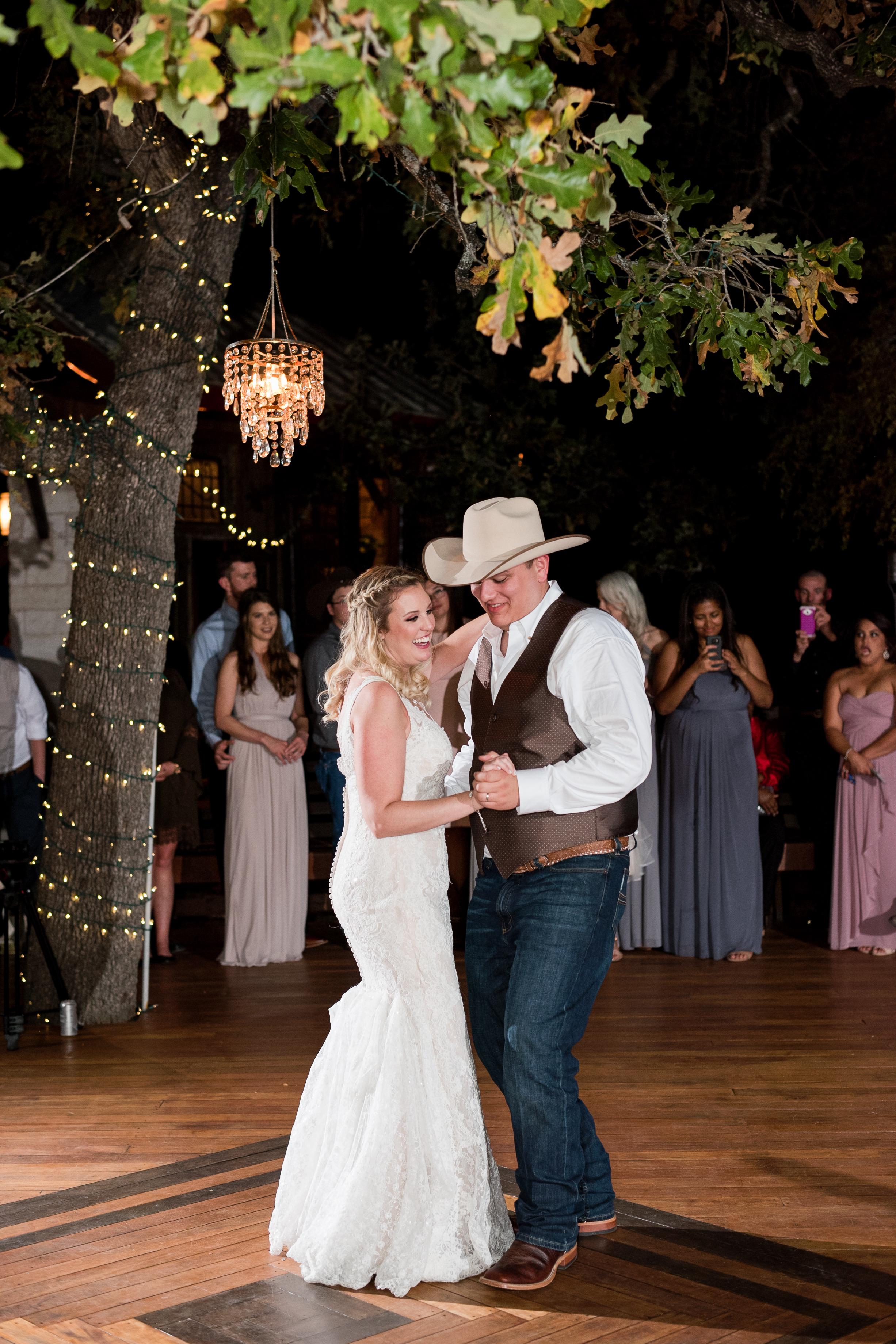 A bride and groom hold hands and dance on the wooden dance floor in Georgetown, Texas at their outdoor wedding.