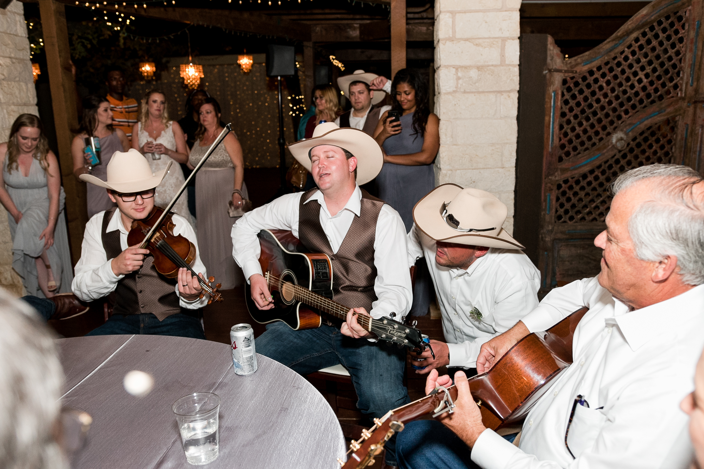 A group of men play live music on guitars at a wedding reception in Georgetown, Texas