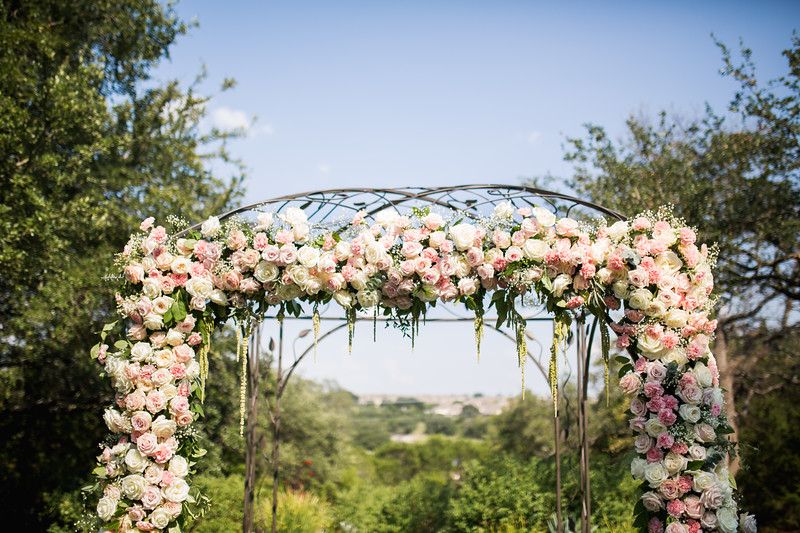 An outdoor wedding arbor in Georgetown, Texas is covered in soft colored florals and greenery.