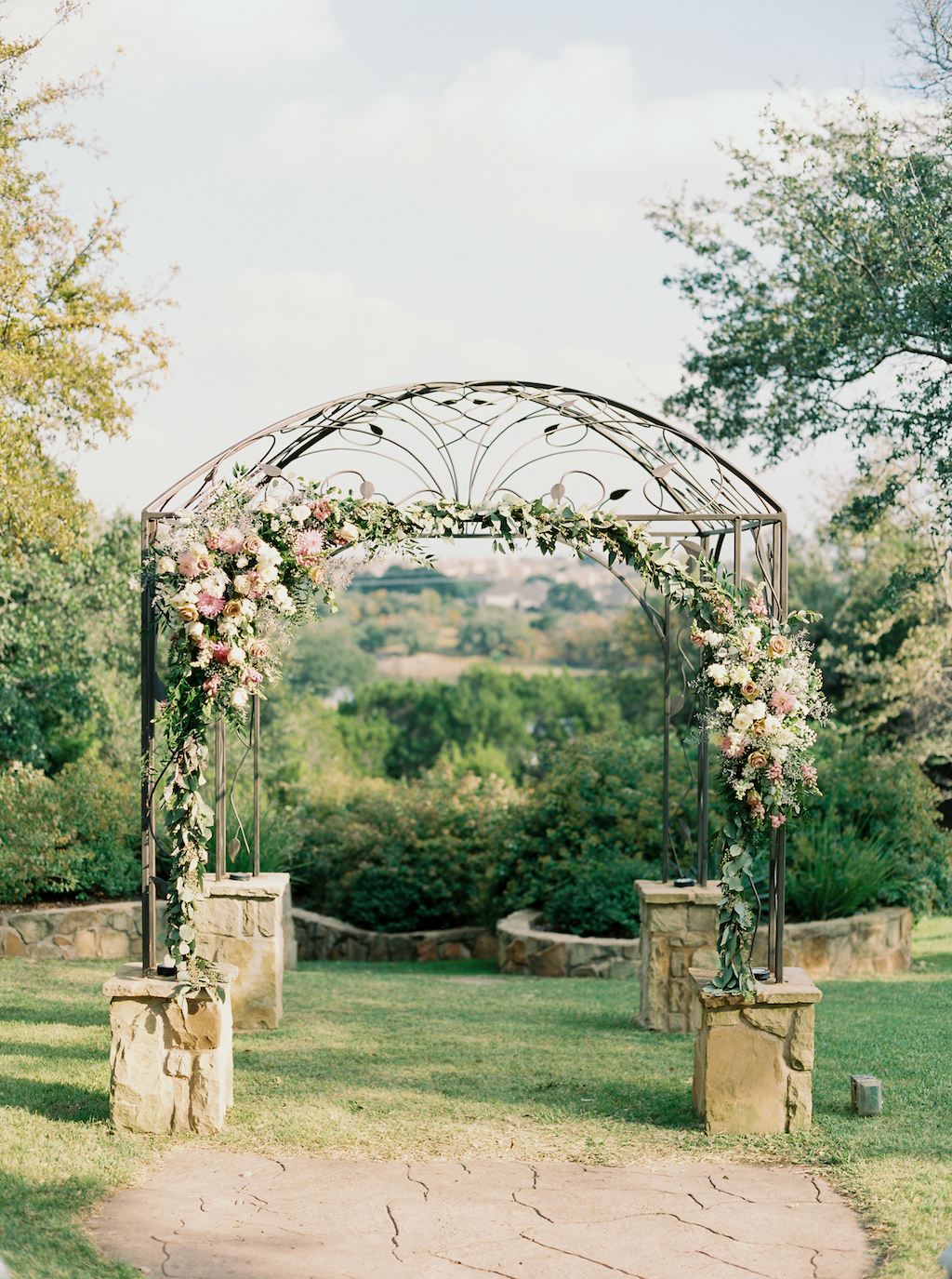 Kindred Oaks, a wedding venue in Georgetown, Texas, features a unique iron arbor at their outdoor ceremony site.