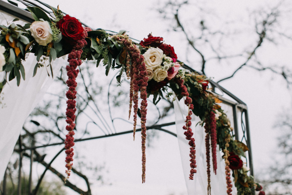 An iron arbor is decorated with red and white florals at an outdoor wedding venue in Georgetown, Texas. Photo by Tim Waters Photography.