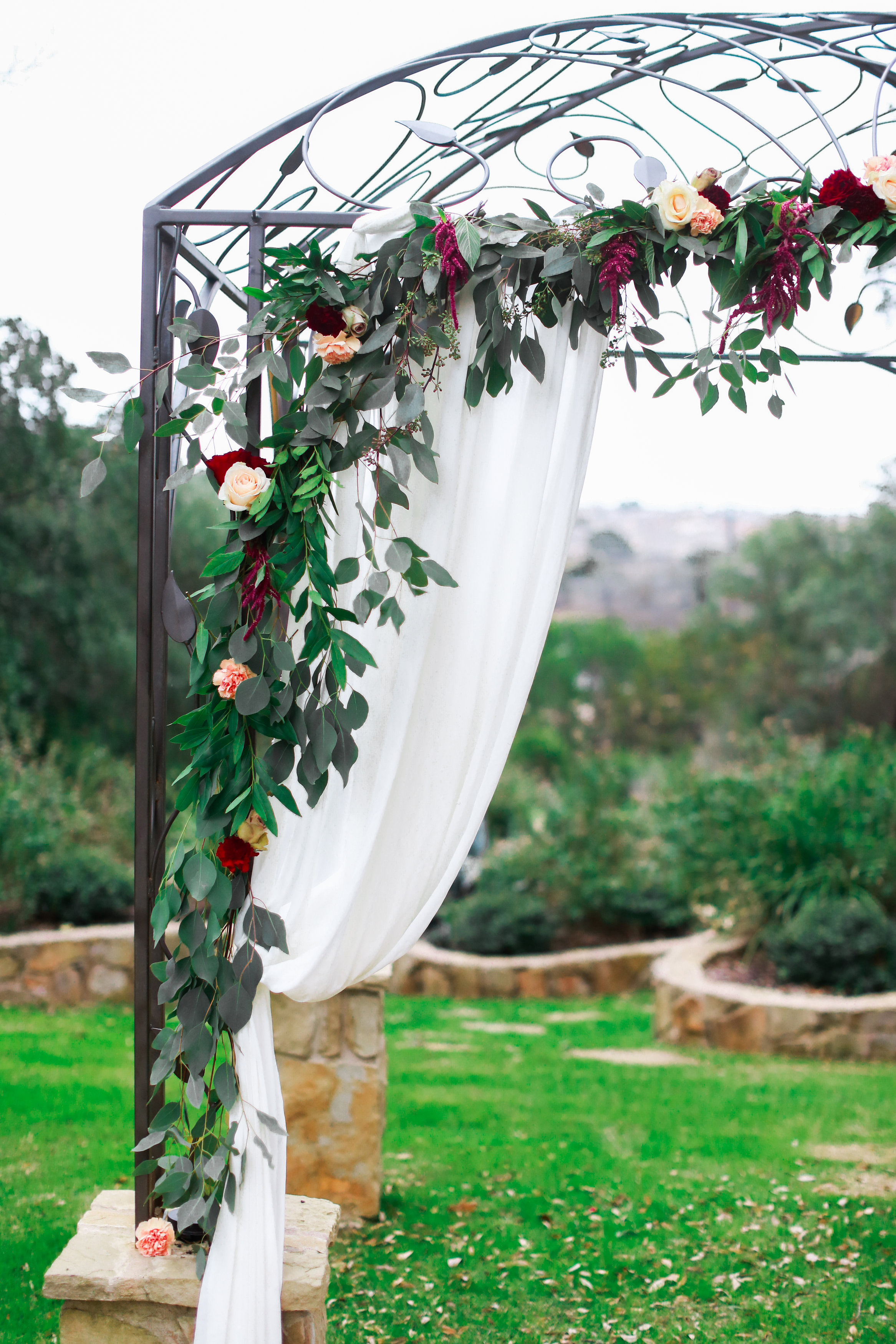 An iron arbor is decorated with white cloth and greenery at a wedding venue in Georgetown, Texas. Photo by Jeff Brummett Visuals.