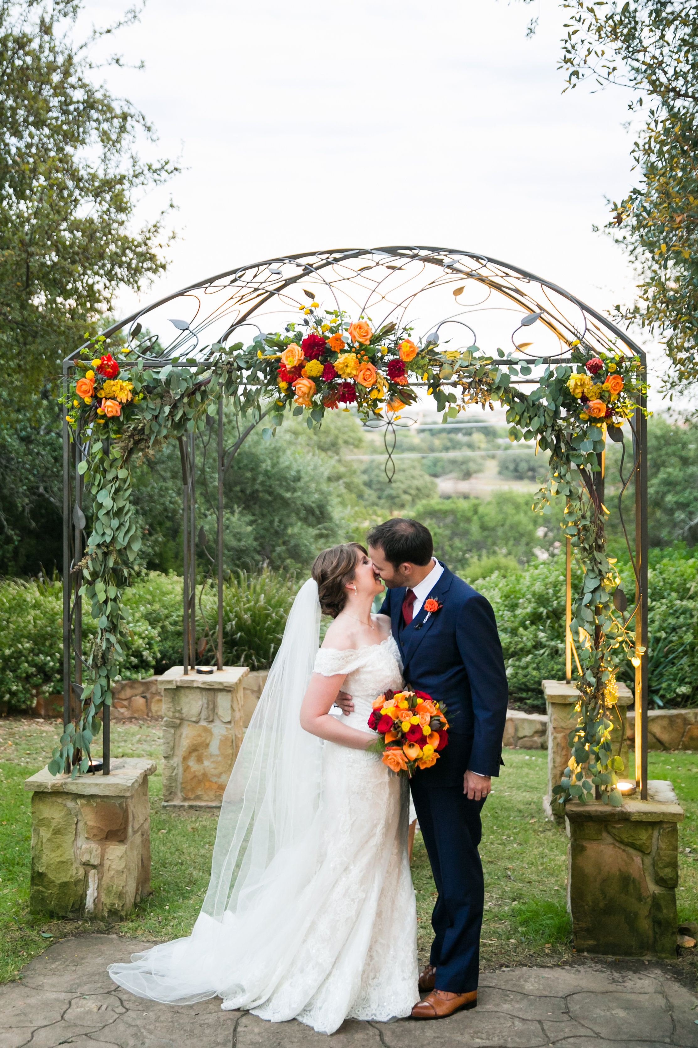 A bride and groom kiss underneath their wedding ceremony arbor at a Georgetown, Texas wedding venue. Photo by Tank Goodness Photography.