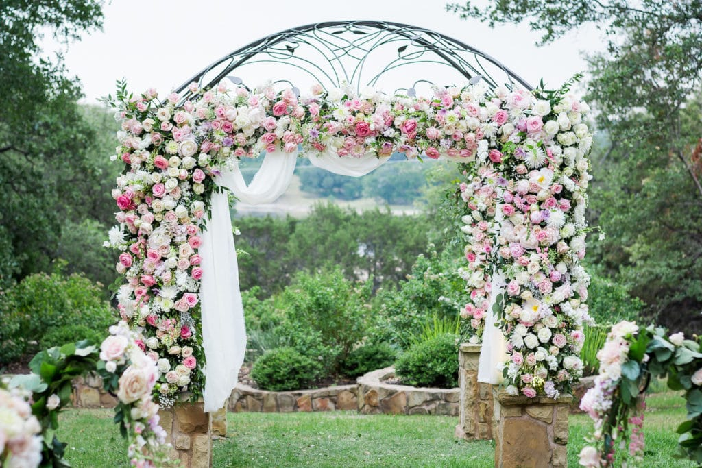 A large wrought iron wedding arbor is covered in layers of pink, white, and purple roses. Floral design by ZuZu's Petals of Austin.