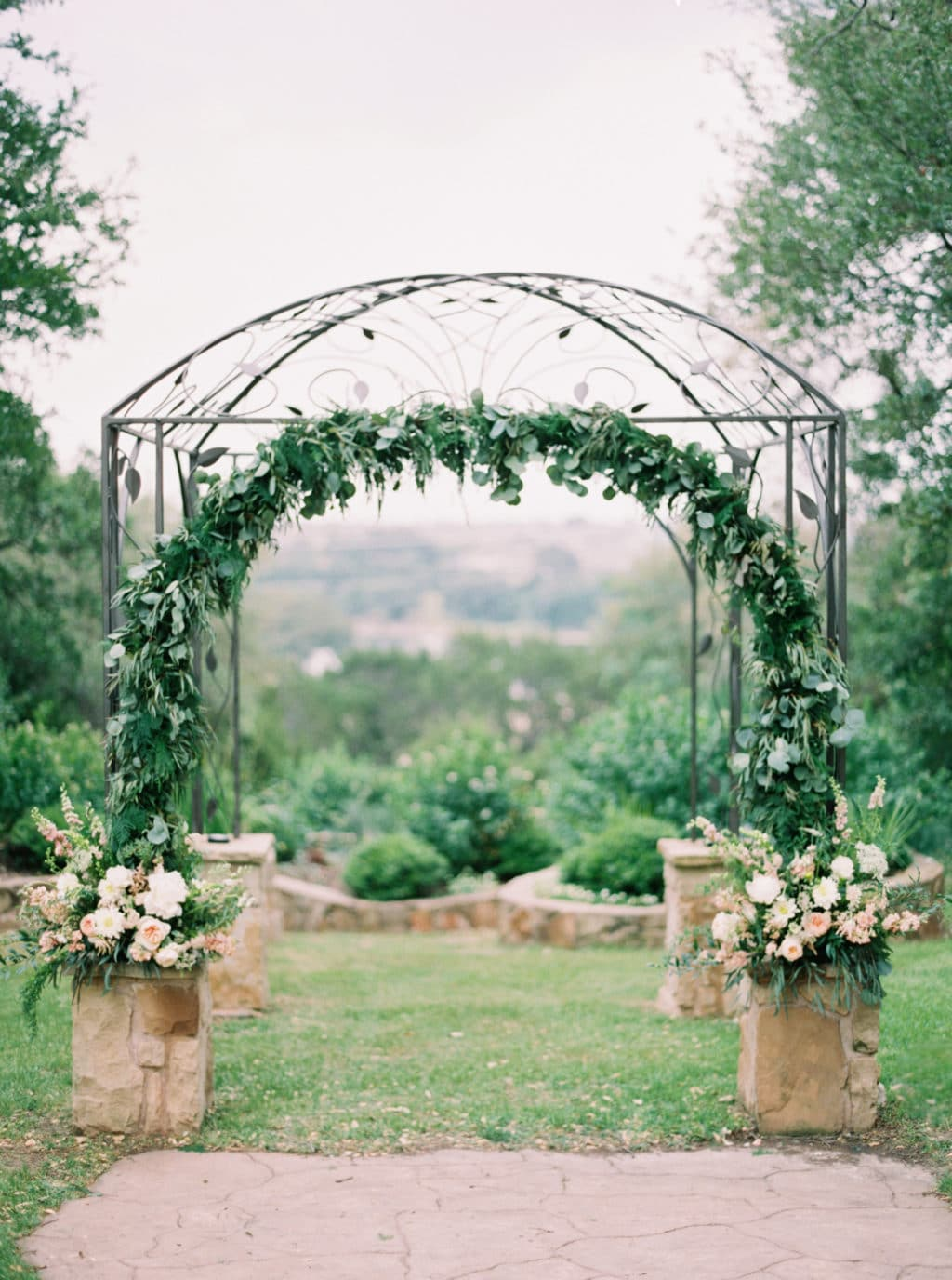 An intricate iron wedding arbor is decorated with an arch of greenery and muted florals at Kindred Oaks in Georgetown, Texas. Photo by Jenna McElroy Photography.
