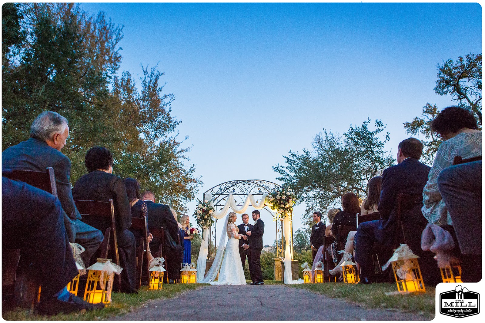 A bride and groom stand under an arbor at the end of a lighted aisle at their evening wedding in Georgetown, Texas. Photo by The Mill Photography Studio.